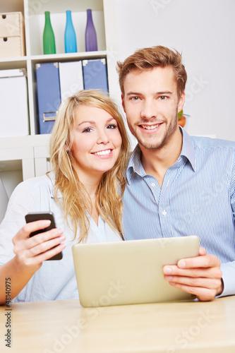 Lachendes Paar mit Tablet PC und Smartphone