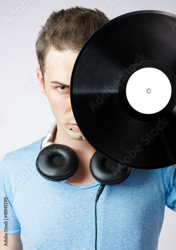 Young man covering his face with a vinyl disc