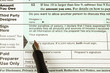 Close up of a U.S. tax form and pen ready to sign signature.
