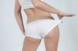 femme soulignant sa solhouette en tirant sur son boxer blanc