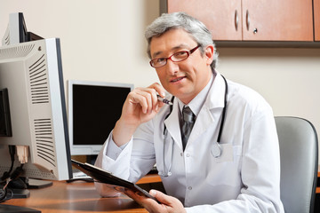Doctor Sitting At Desk In Front Of Computer