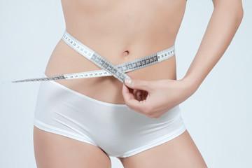 femme mesurant son ventre plat en boxer blanc