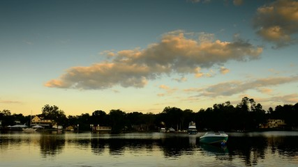 Timelapse of Evening Sky, lake, homes along river bank