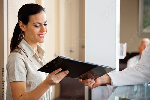Receptionist Taking Clipboard From Doctor