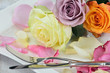 Romantic place setting with rose petals and roses