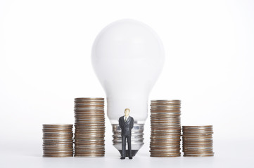 Businessman figurine standing in front of light bulb and coins