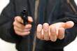 拳銃を持って金品を要求する強盗犯