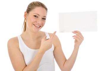 Junge Frau in weißer Kleidung zeigt auf leeres Schild