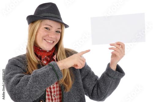 Junge Frau in bayrischer Kleidung zeigt auf leeres Schild