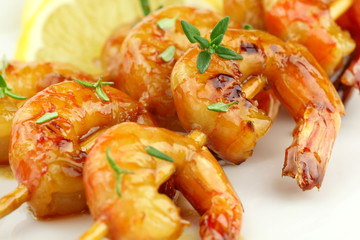 Glazed shrimp skewers with thyme and lemon closeup
