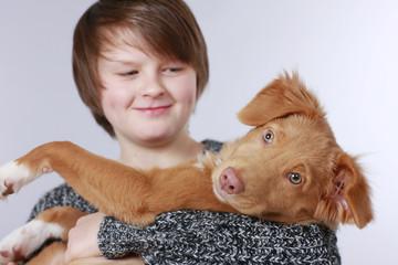 Glücklicher Junge hält seinen Hund im Arm