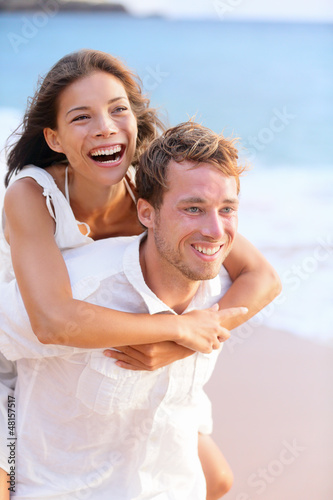 Happy couple piggybacking on beach.