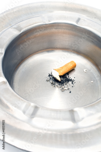 Cigarette butt in a metal ashtray