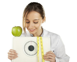 nutritionist watching and holding a weight scale and green apple