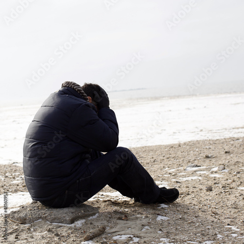 Lonely man sitting on sand