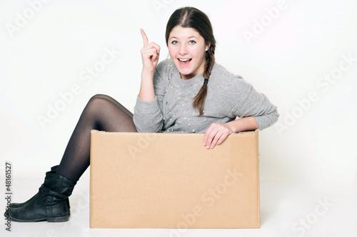 junges freches Mädchen sitzt in einem Karton