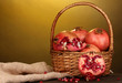 Ripe pomegranates on basket on wooden table on yellow