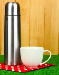 metal thermos with cup on grass on wooden background