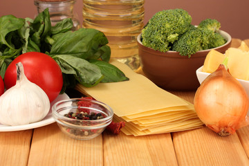 Vegetarian lasagna ingredients on brown background