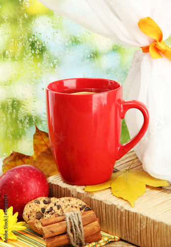 cup of hot tea and autumn leaves, on rain background