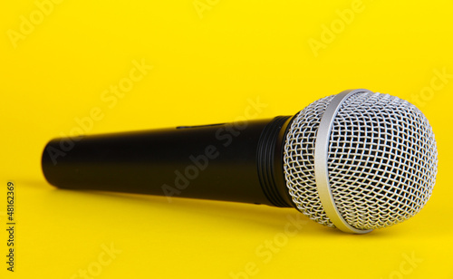 Black microphone on yellow background