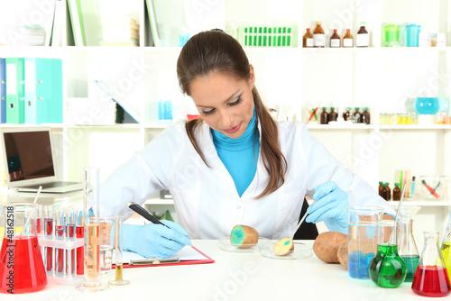 Young female scientist injecting GMO into   potato in