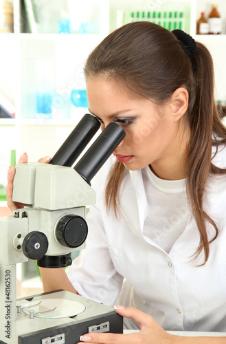 Young scientist looking into  microscope in  laboratory.