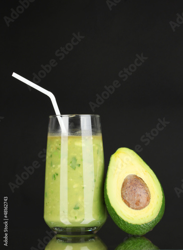 Useful fresh avocado and half avocado on black background