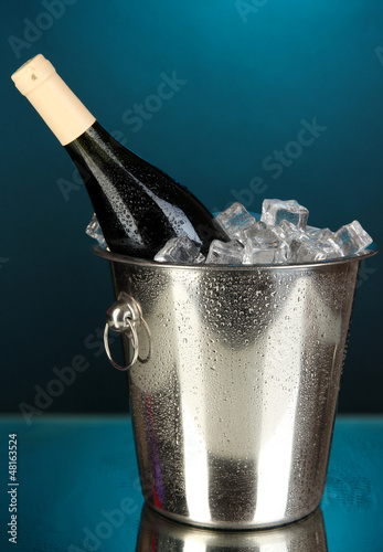 Bottle of wine in ice bucket on darck blue background