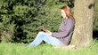 woman with digital tablet resting in the park