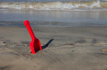Red shovel at the beach