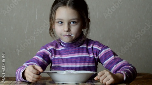 girl with an appetite for eating with a spoon porridge