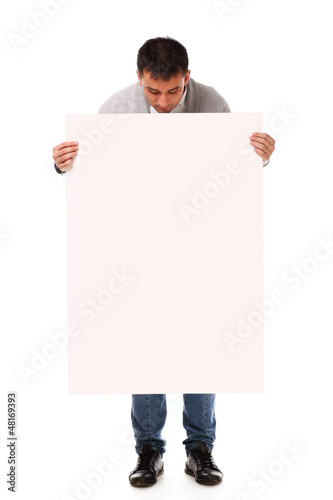 Young handsome man holding blank board
