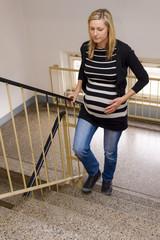 schwangere Frau geht eine Treppe rauf