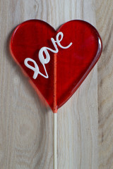 Heart lollipop on wooden background