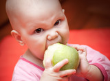 Funny little hungry baby greedily eats green apple