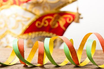 Holzbrett mit bunten Luftschlangen und Karnevalsmütze
