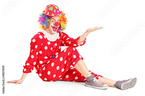 Clown with smiling joyful expression sitting down and gesturing