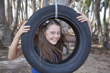 young girl playing with tyre swing