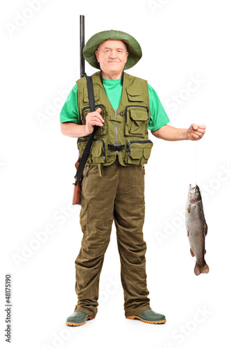 Full length portrait of a male hunter with rifle holding a fish