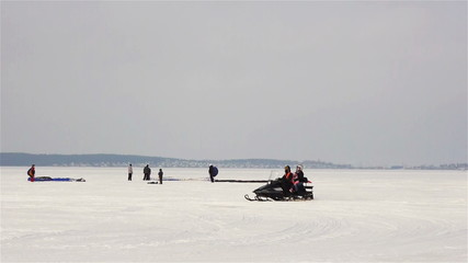 Riding motosledge snowmobile on winter lake