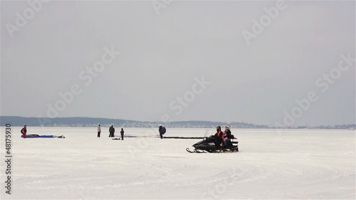 Riding motosledge snowmobile on winter lake