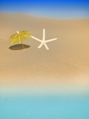 Beach Umbrella standing in the Sand with a Starfish near