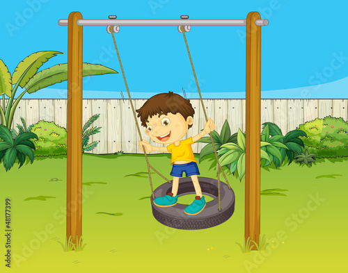 A boy swings on a wheel