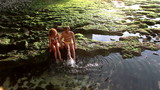 Happy couple making splashes by legs while Bali trip
