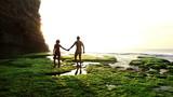 Cheerful couple in love walking on Bali lagoon