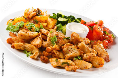 Grilled meat and vegetables on white background