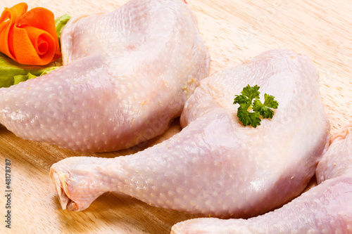 Raw chicken legs on cutting board