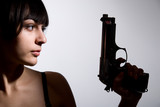 Close-up portrait of sexy woman with gun