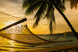 Fototapety Hammock silhouette with palm trees on a beach at sunset